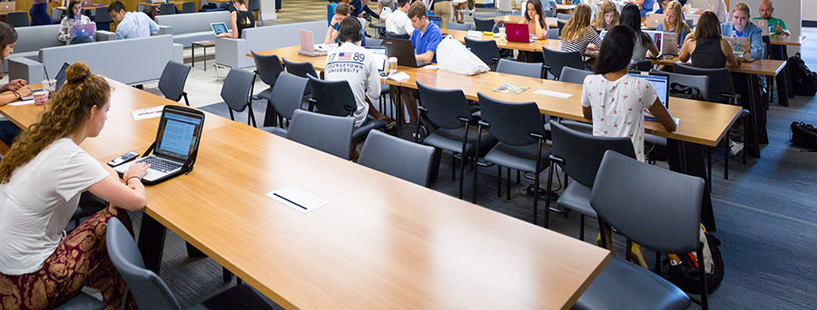 Students on their laptops in the library